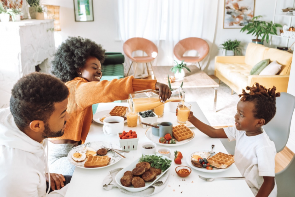 A family sits in a brightly lit kitchen eating a breakfast of waffles, fruit, sausage, and eggs. The mother is pouring juice into her child's outstretched cup.